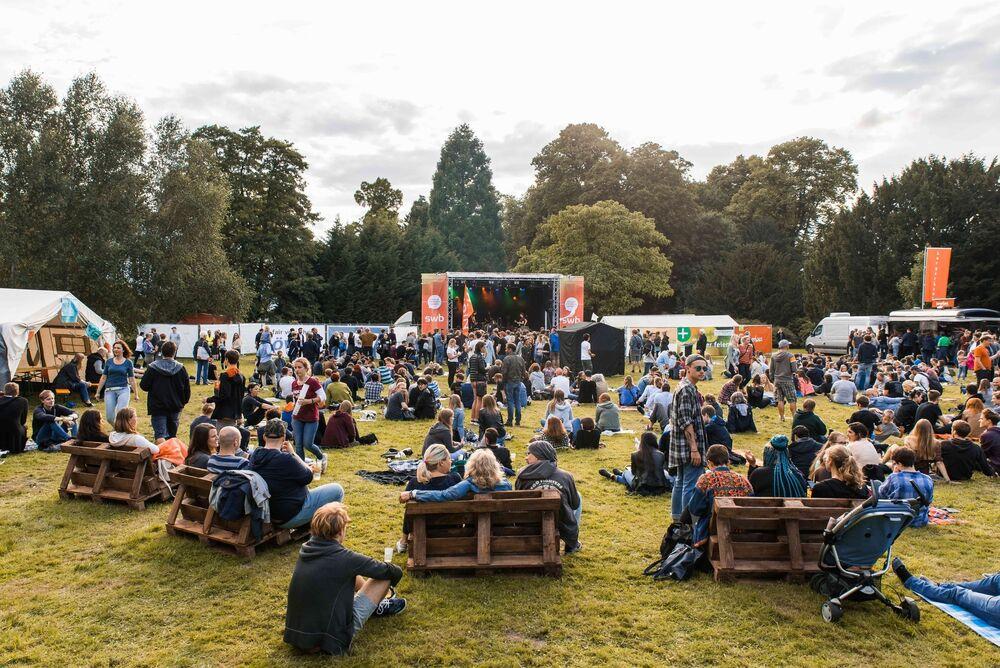 Foto: Viele Menschen sitzen auf dem Gras und warten auf einen Konzert -