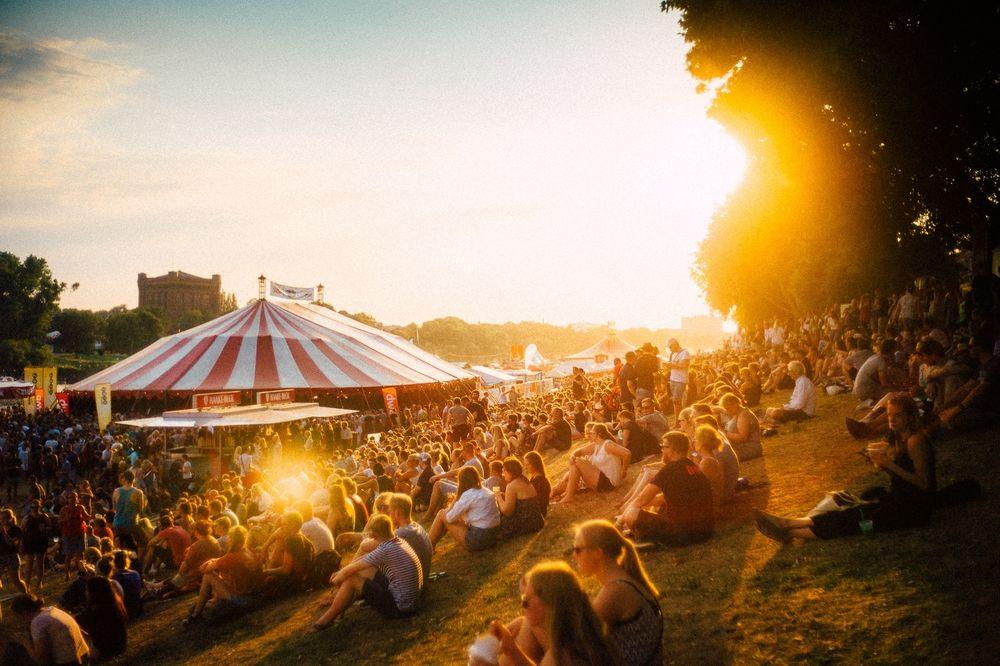 Menschen sitzen vor einem Zelt bei dem Sonnenuntergang -